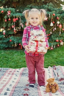 Child girl  with gifts near a christmas tree, christmas in july on nature