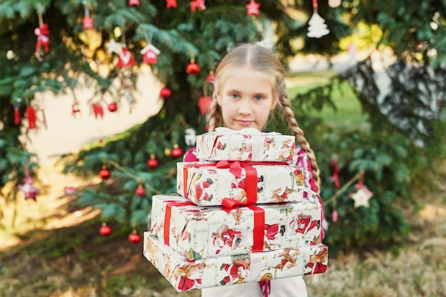 Child girl with gifts near a christmas tree