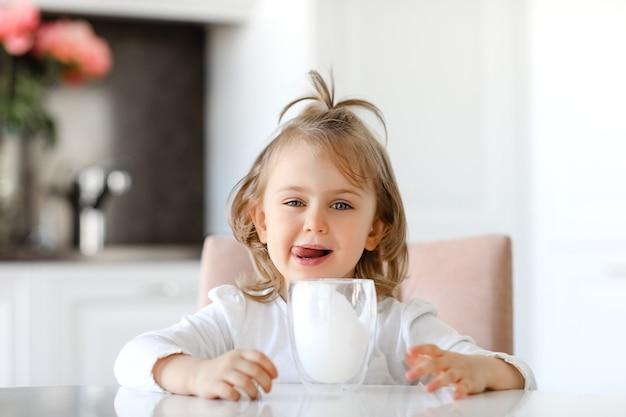 唇にミルクの口ひげとキッチンの白いテーブルに座っているミルクのガラスを持つ子供の女の子¡
