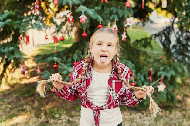 Child girl with pigtails at the christmas in july photo shoot on the background of a christmas tree with gifts