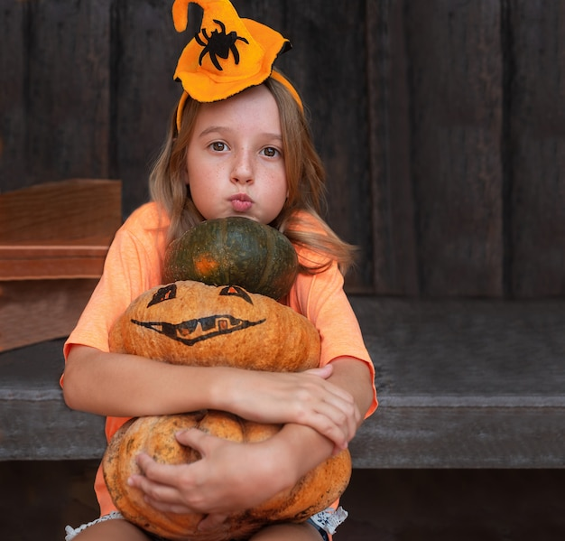 Child girl with pumpkins in halloween decorations on a wooden background