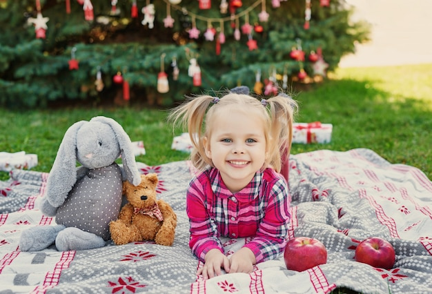 Child girl with soft toys on a plaid near a christmas tree, christmas on nature