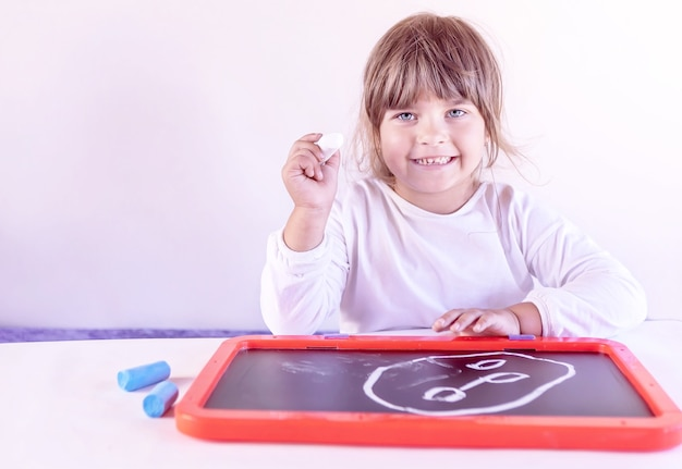 A child a girl with white chalk in her hands smiles in front of her drawing on the board