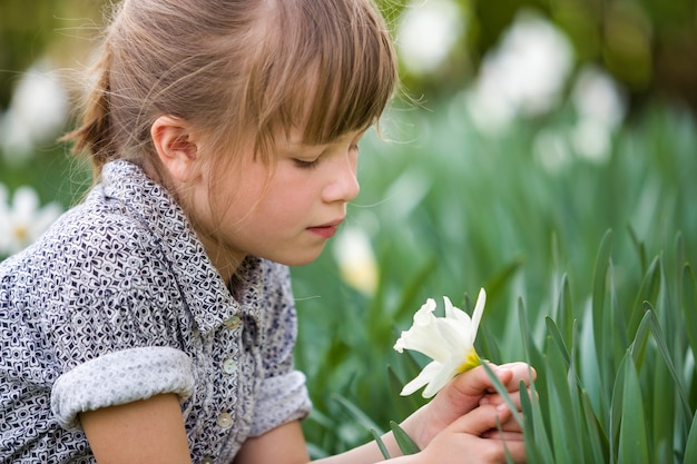 Child girl with white daffodil flower on sunny summer day.