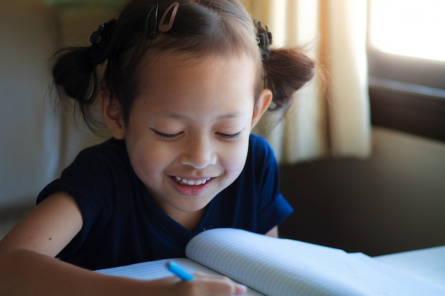 Child girl writing on the book with smile.