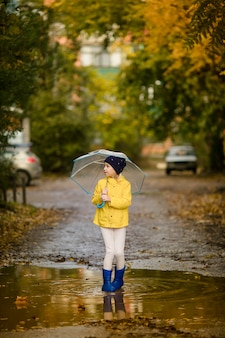 Child girl in yellow jacket and blue boots with umbrella runs through the autumn puddle
