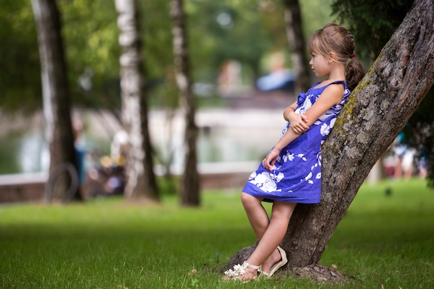 Child girlleaning on tree trunk.