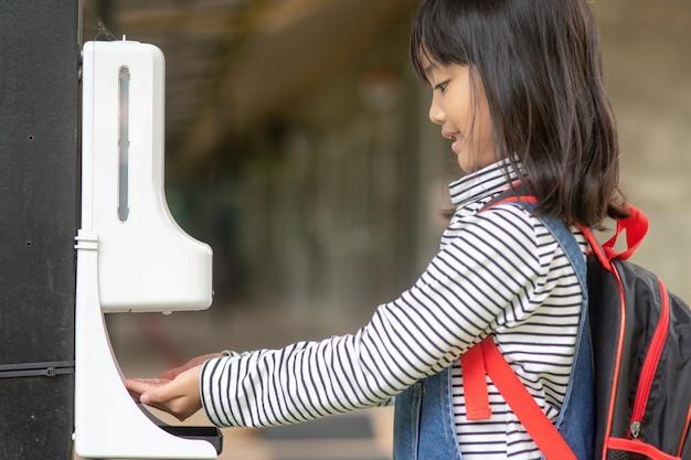 자동 알코올 젤 디스펜서를 사용하여 손 소독제 기계 살균 소독제를 분사하는 어린 소녀들, 코로나바이러스 covid-19 전염병 이후의 새로운 일상.