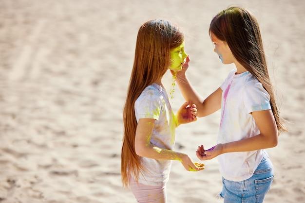 色粉をまぶした女児がホーリー祭を祝う