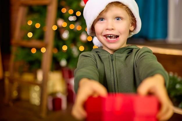 Ребенок дарит рождественский подарок на фоне новогодней елки