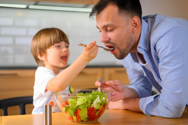 Child giving his father salad to eat