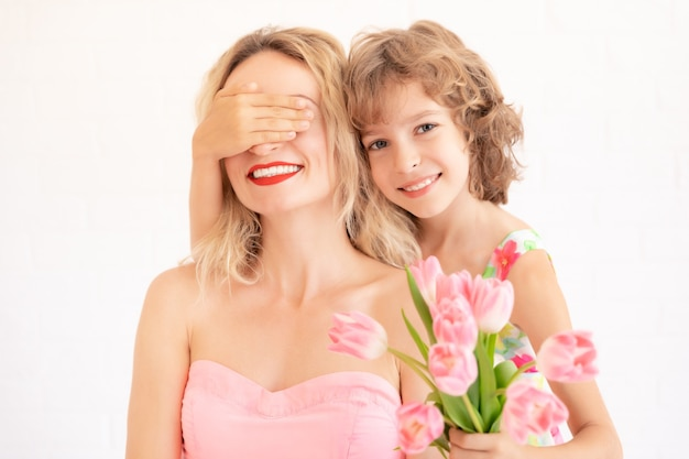 Ребенок дает женщине букет тюльпанов