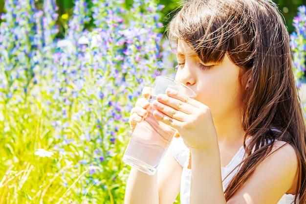 子グラスの水。セレクティブフォーカス。子供の自然