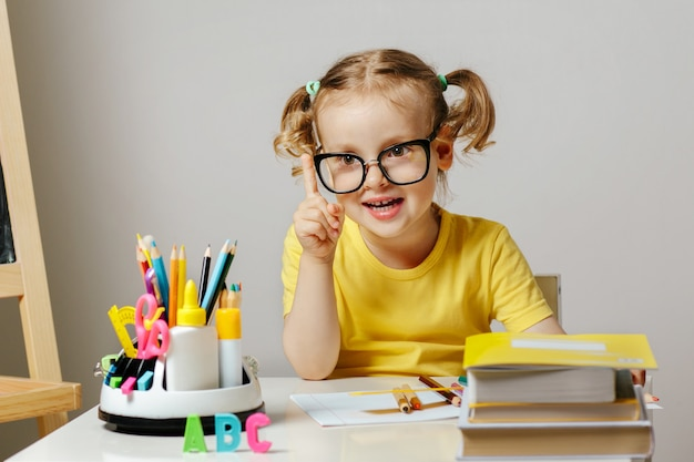 Child in glasses in the classroom with school supplies pencils and book