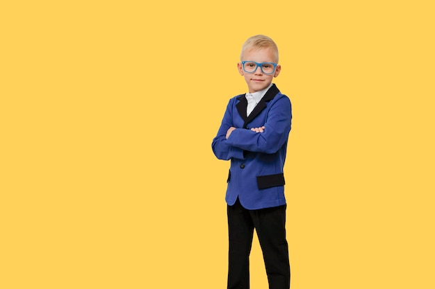 Child in glasses from elementary school on yellow