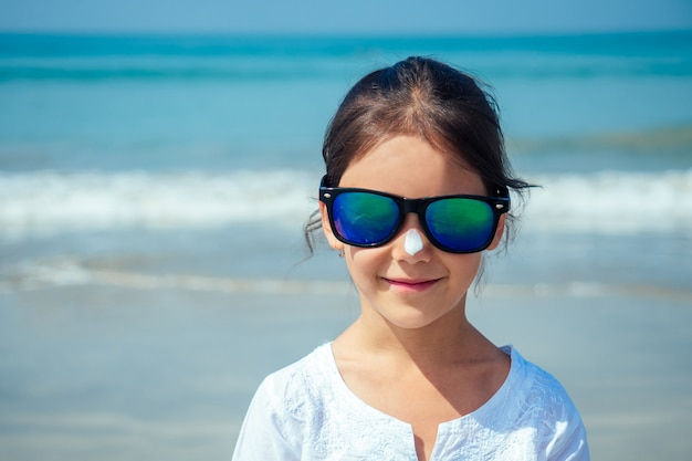 Child in glasses standing on the beach.