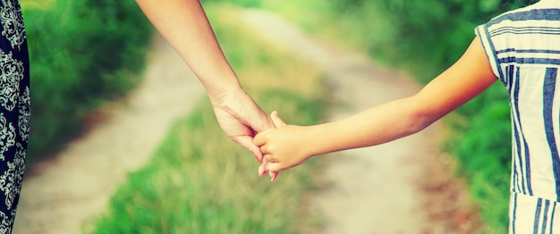 Child goes hand in hand with his mother. selective focus.