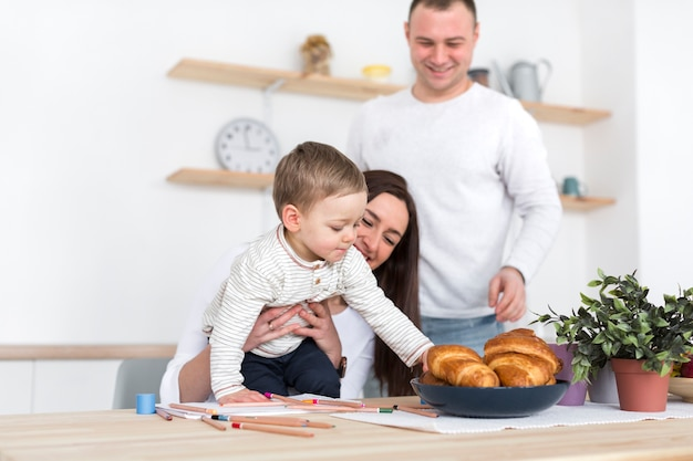 台所で親とクロワッサンをつかむ子 無料写真