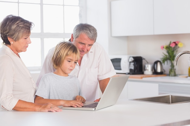 Child and grandparents looking at laptop