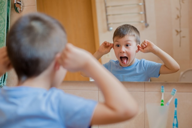 The child grimaces before the mirror in the bathroom.
