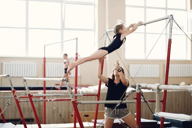 어린이 체조 균형 빔. 체조 대회에서 운동 가로 막대 동안 여자 체조 선수. 자녀와 함께 코치하십시오.