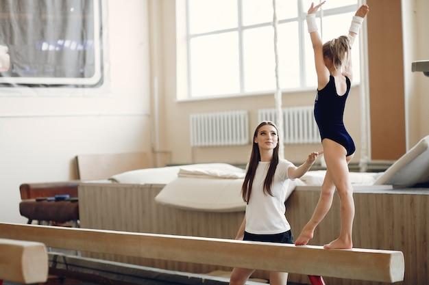 Бревно-балансир детской гимнастики. спортсменка гимнастка во время турника упражнения в соревнованиях по гимнастике. тренер с ребенком.