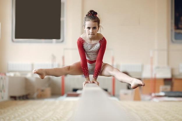 Бревно-балансир детской гимнастики. спортсменка гимнастка во время турника упражнения в соревнованиях по гимнастике.
