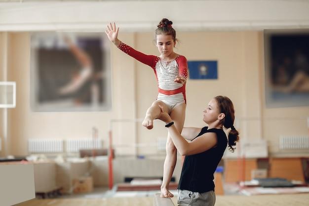 Fascio di equilibrio di ginnastica del bambino. atleta ginnasta ragazza durante una barra orizzontale di esercizio nelle competizioni di ginnastica. allenatore con bambino.