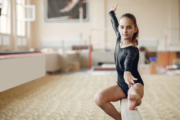 Child gymnastics balance beam.  girl gymnast athlete during an exercise horizontal bar in gymnastics competitions.