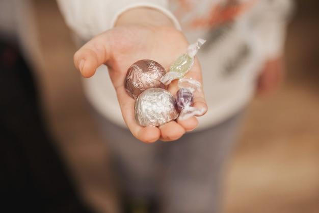 子供の手はゲストを扱うためにキャンディーを差し出します。カラフルなお菓子を手にした小さな男の子は、居心地の良い快適さとおもてなしを象徴しています。ゲストを招待し、贈り物をするというコンセプト。セレクティブフォーカス。コピースペース