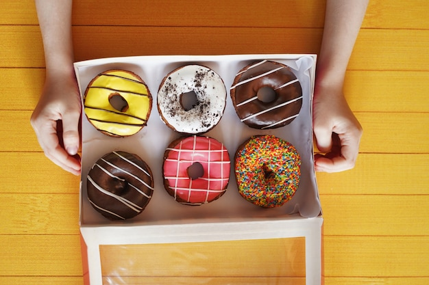 Child hand holding box with sweet donut dessert.