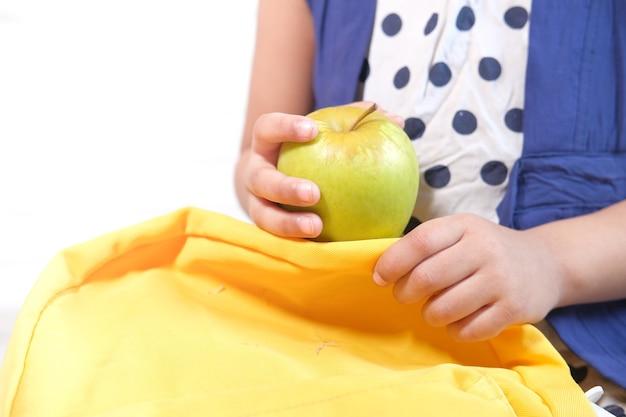 白い壁に青リンゴを持っている子の手