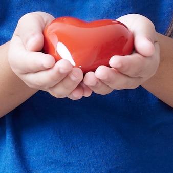 赤いハートを持っている子の手