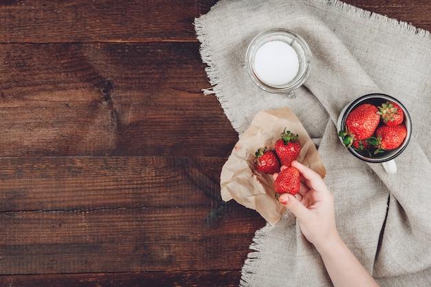 Child hand holding strawberry