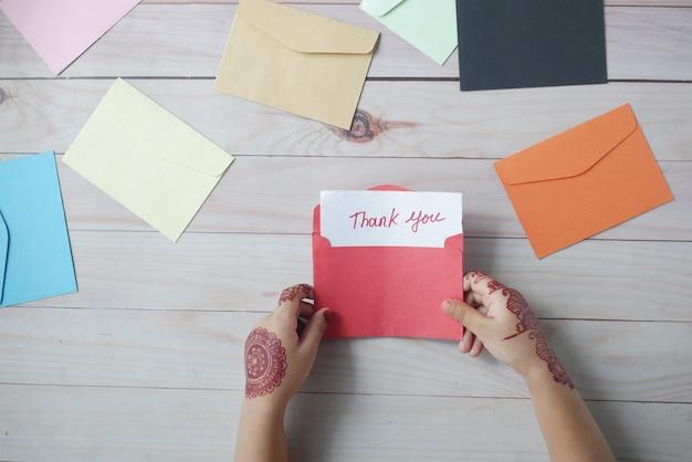 Рука ребенка, держащая благодарственное письмо на столе
