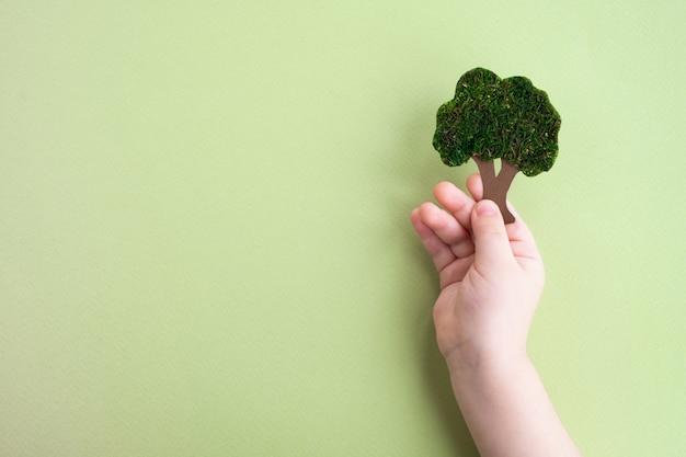 子供の手は、コピースペースで緑の背景に分離された装飾的な木を保持します。