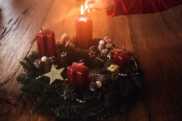 クリスマスの4週間前に、アドベントリースの最初のキャンドルを伝統として子供が手で照らします