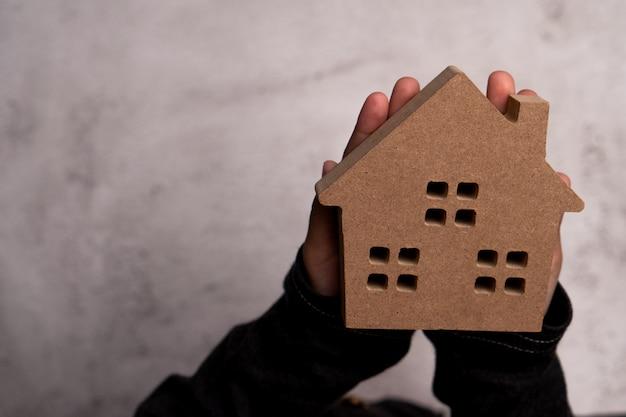 Человек руки ребенка держа деревянный модельный дом. концепция любви семьи и безопасности защиты,