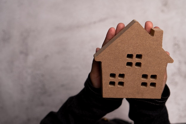 Child hand man holding a wooden model house. concept of love family and security protection,