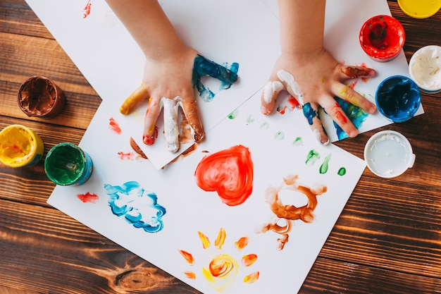 Child hand painting colorful mosaic the child is drawing on white sheets with finger paints