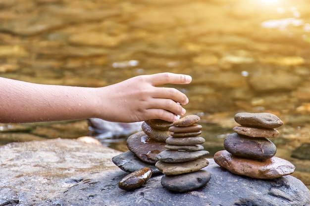 Детская рука кладет камни на вершину пирамиды на ручье