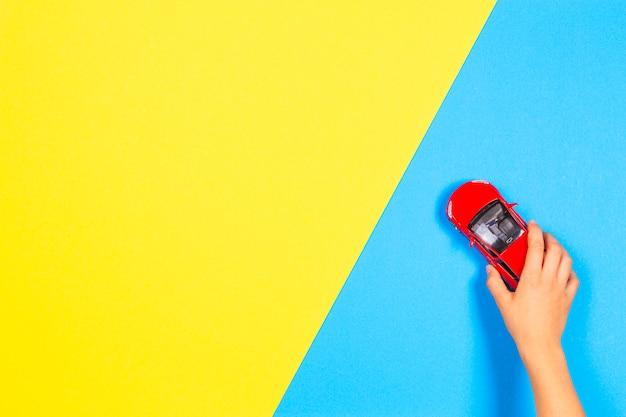 明るい青と黄色の背景に赤いおもちゃの車で遊ぶ子供の手