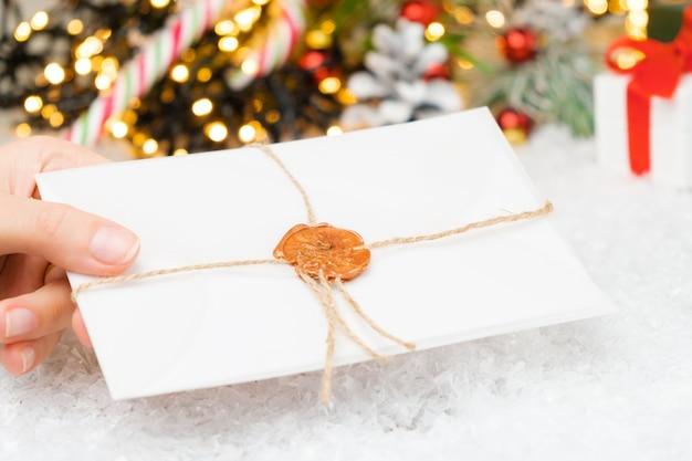 クリスマスツリーの下にワックススタンプでサンタクロースへの手紙と封筒を置く子供の手。