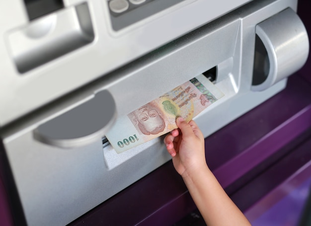Child hand receive money from atm