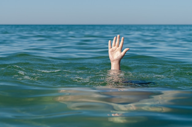 Child hand at sea, need for help.