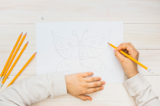 Child hand sketching butterfly with pencil on wooden background