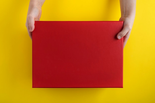 Child hands hold large red box on yellow background. copy space. mock up.