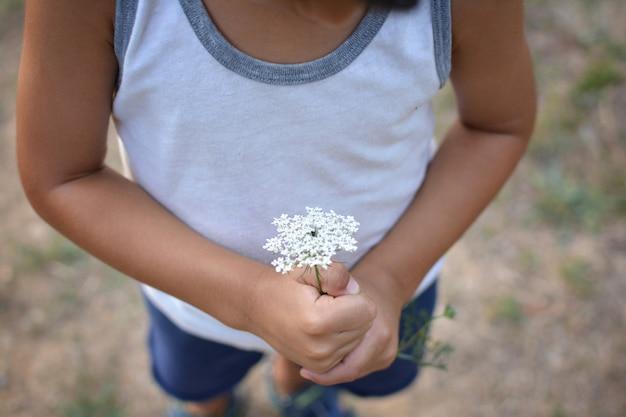 Детские руки, держащие цветок