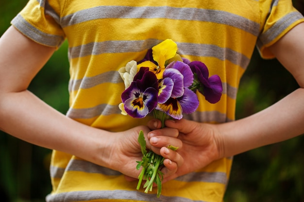 Child hands holding a bouquet pansies flower . back view.focus for flowers