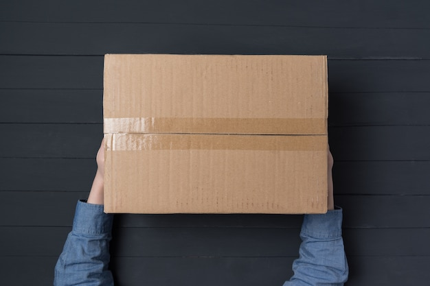 Child hands holding large cardboard box. delivery of parcels to house.
